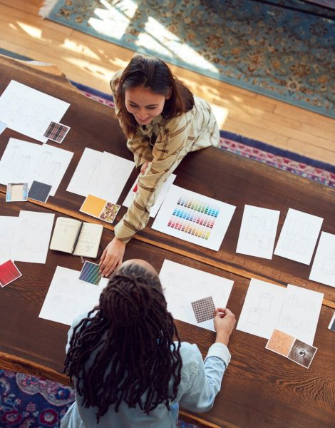 Overhead View Of Two Women Having Creative Design Meeting Around Wooden Table In Office